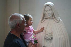 Petite fille dans les bras de son papa, la main sur la statue de Jeanne Jugan