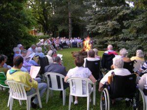 groupe de personnes âgées, jeunes et Petites soeurs autour d'un feu