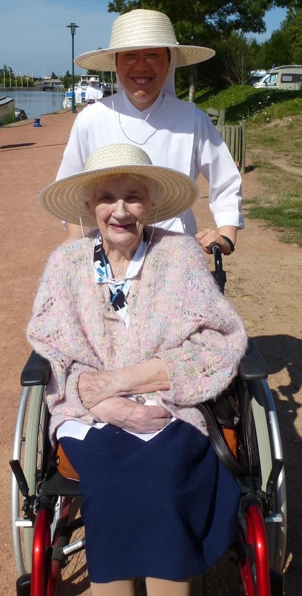 Petite Soeur poussant une résidente en fauteuil roulant