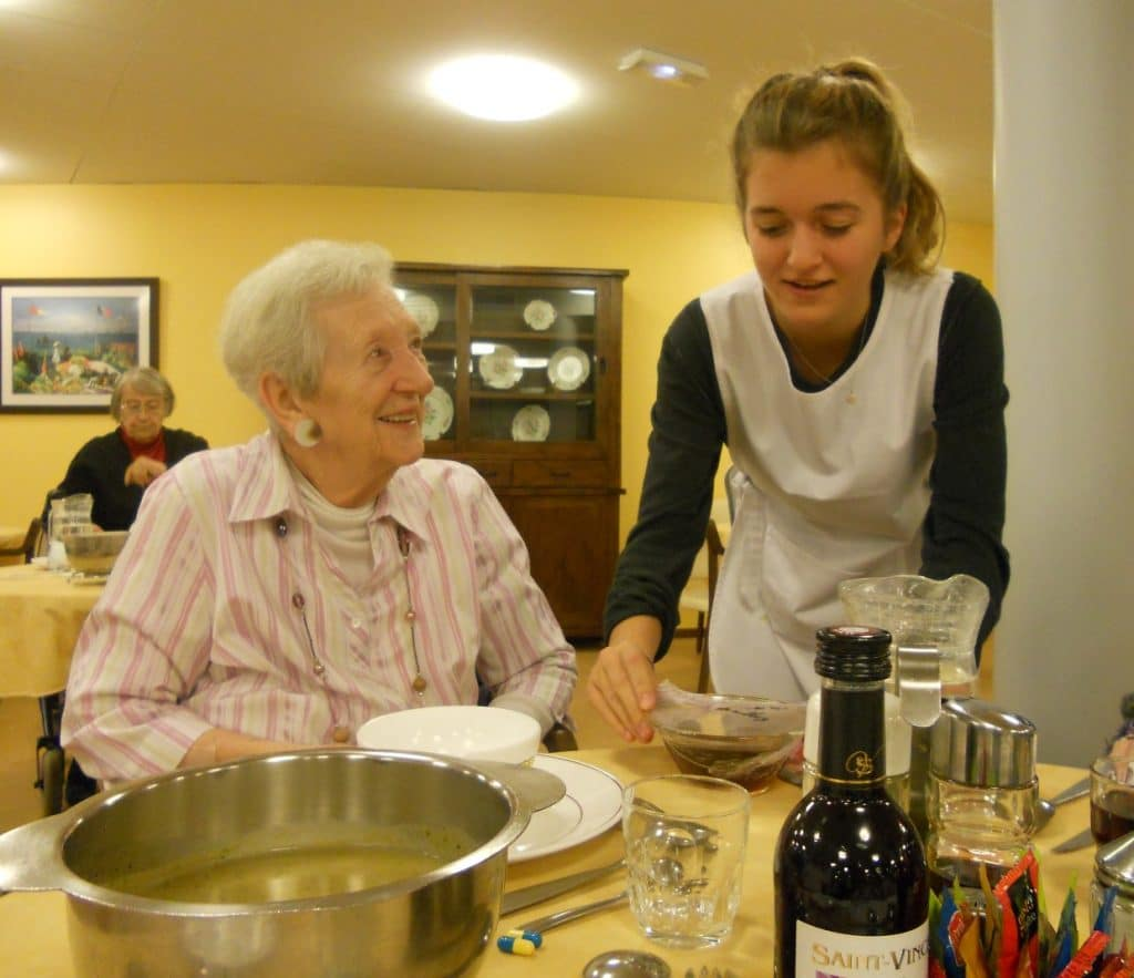 Jeune fille servant une résidente à la salle à manger