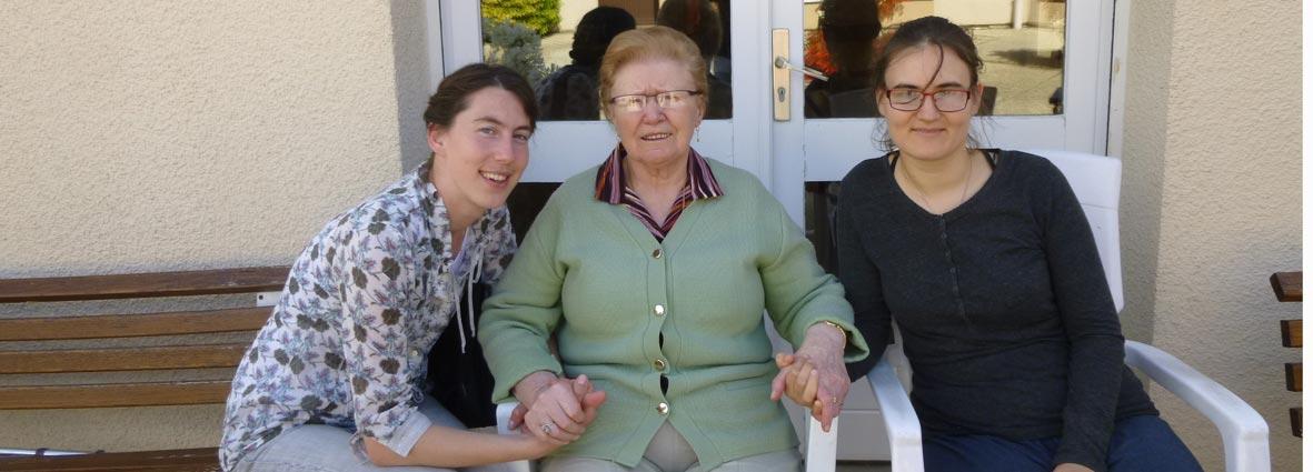 deux jeunes filles entourant une personne âgée