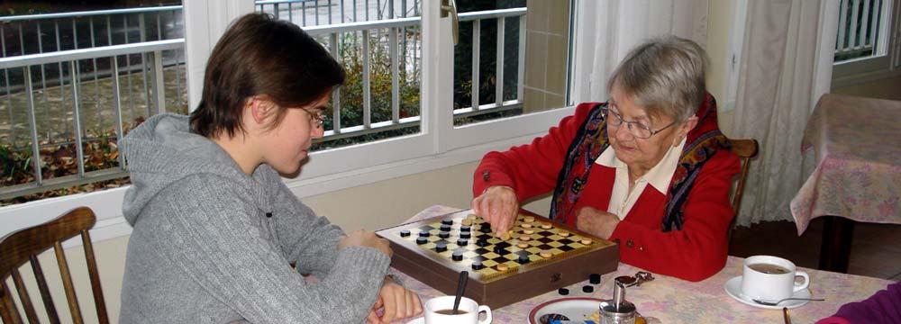 jeune fille et personne âgée jouant au jeu de dames