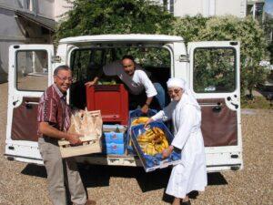 bénévoles et petite soeur rentrant de la quête aux fruits et légumes