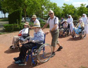 bénévole, petites soeurs poussant des personnes âgées en fauteuil roulant pour une promenade