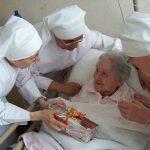 trois petites soeurs autour d'une personne âgée malade, lui offrant un cadeau pour son anniversaire