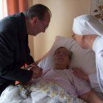 Personne âgée alitée, avec un prêtre et une petite soeur à son chevet